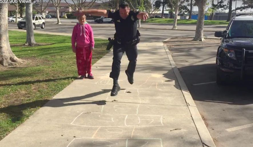 In this Wednesday, March 30, 2016 still frame from video provided by the Huntington Beach, Calif., Police Department, Officer Zach Pricer shows an 11-year-old homeless girl how to hopscotch on a street in Huntington Beach, Calif. Officers found the girl and her mother living in a car in a parking lot Wednesday. While other officers reached out to the department's homeless task force, Pricer turned to hopscotch to make the girl feel more comfortable, knowing a police officer can seem scary to a child. (Huntington Beach Police Department via AP)
