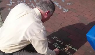 Emory University President James W. Wagner chalked his own free speech message onto a campus sidewalk after students protested over pro-Donald Trump messages that they said threatened their safety. (YouTube/@TheFIREorg)