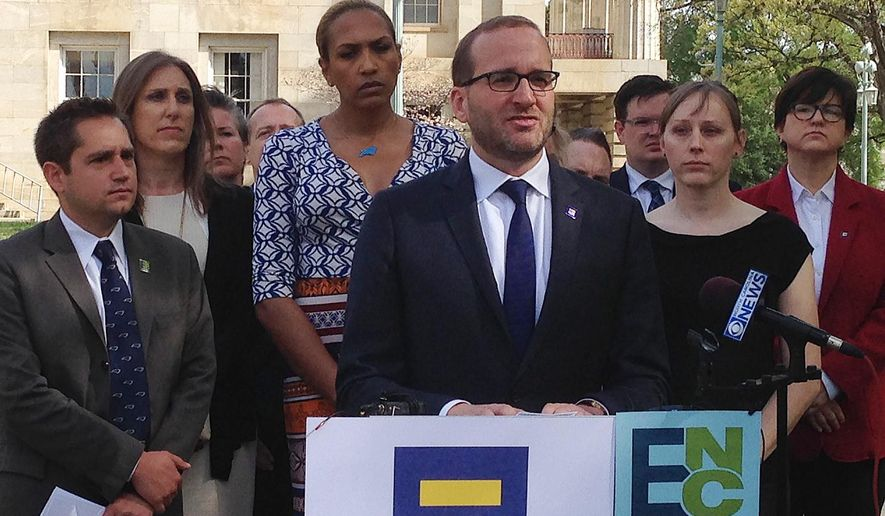 Human Rights Campaign Executive Director Chad Griffin, center, speaks at a news conference at the old state Capitol Building in Raleigh, N.C. on Thursday, March 30, 2016. Griffin, Equality North Carolina Executive Director Chris Sgro, far left, and others delivered a letter to Gov. Pat McCrory signed by more than 100 corporate executives calling for repeal of a law limiting bathroom options for transgender people and prohibiting local anti-discrimination measures providing protections on the basis of sexual orientation and gender identity. (AP Photo/Gary Robertson)