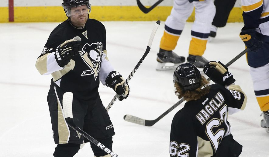 Pittsburgh Penguins' Phil Kessel (81) celebrates his goal with teammate Carl Hagelin (62) during the first period of an NHL hockey game against the Nashville Predators in Pittsburgh, Thursday, March 31, 2016. (AP Photo/Gene J. Puskar)