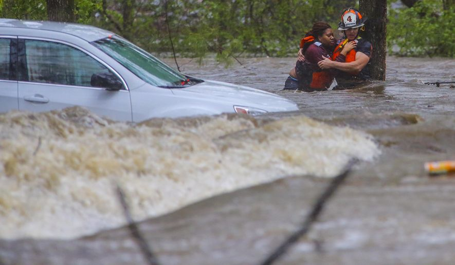 Little Rock Fire Capt. Steve Kotch, right, uses a cable safety line to rescue an unidentified woman from her flooded car in Boyle Park in Little Rock, Ark., during heavy rainfall Wednesday, March 30, 2016. Lightning and heavy rains hit central Arkansas during the evening rush hour. (Stephen B. Thornton/The Arkansas Democrat-Gazette via AP) ARKANSAS TIMES OUT; ARKANSAS BUSINESS OUT; MANDATORY CREDIT