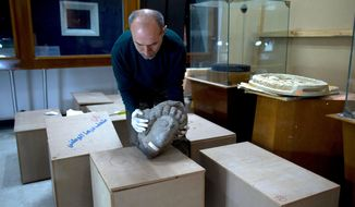 In this Tuesday, Feb. 23, 2016 photo, Jihad Abu Kahrlah, an archaeologist at the National Museum in Damascus, Syria, works on preserving artifacts rescued from the Daraa Museum in southern Syria. Faced with the Islamic State group onslaught and destruction by looters, Syrian antiquities authorities succeeded in evacuating hundreds of thousands of artifacts from museums around the country to safety in Damascus. (AP Photo/Hassan Ammar)