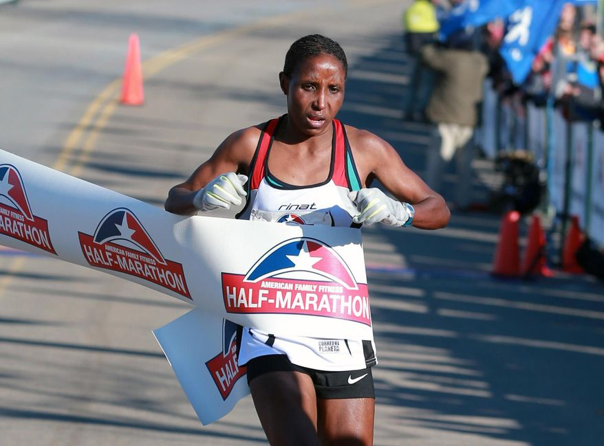 FILE - In this Nov. 15, 2014, file photo, Lilian Mariita, of Kenya, wins the women's division of a half-marathon in Richmond, Va. The 27-year-old's racing career is over, and now she is back at square one: in Nyaramba, the muddy tea-plantation village in western Kenya she thought she'd escaped in 2011, when she left for the promise of a new life pounding American roads. (Daniel Sangjib Min/Richmond Times-Dispatch via AP) /Richmond Times-Dispatch via AP) MANDATORY CREDIT
