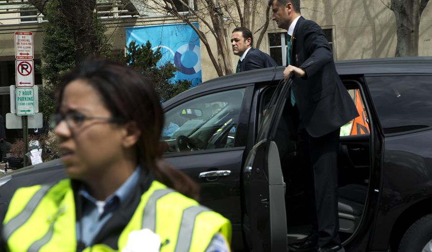 Turkish security stand on the side of a vehicle during a rally outside the Brookings Institution in Washington, Thursday, March 31, 2016, where Turkish President Recep Tayyip Erdogan spoke.  (AP Photo/Manuel Balce Ceneta)