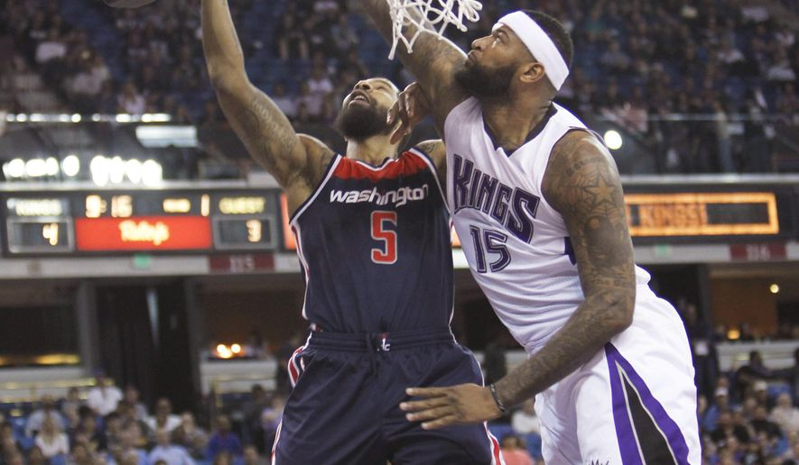 Washington Wizards forward Markieff Morris (5) goes to the basket against Sacramento Kings defender DeMarcus Cousins (15) during the first half of an NBA basketball game in Sacramento, Calif., Wednesday, March. 30, 2016. (AP Photo/Steve Yeater)