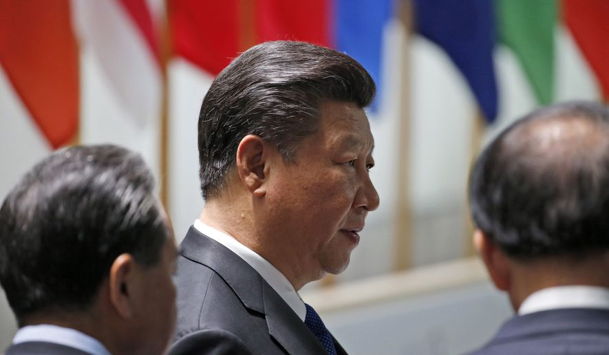 Chinese PresidentXi Jinping, center, prepares to participate in the afternoon plenary session of the Nuclear Security Summit, Friday, April 1, 2016, in Washington. (AP Photo/Alex Brandon)