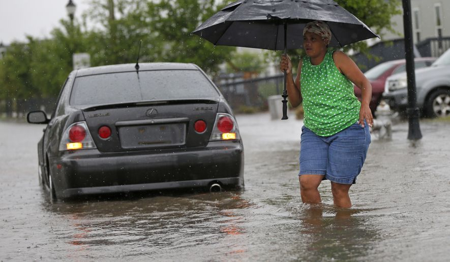 Andrea Jones walks past a stranded car to get to her vehicle in receding street flooding, after severe rainstorms moved through New Orleans, Friday, April 1, 2016. (AP Photo/Gerald Herbert)