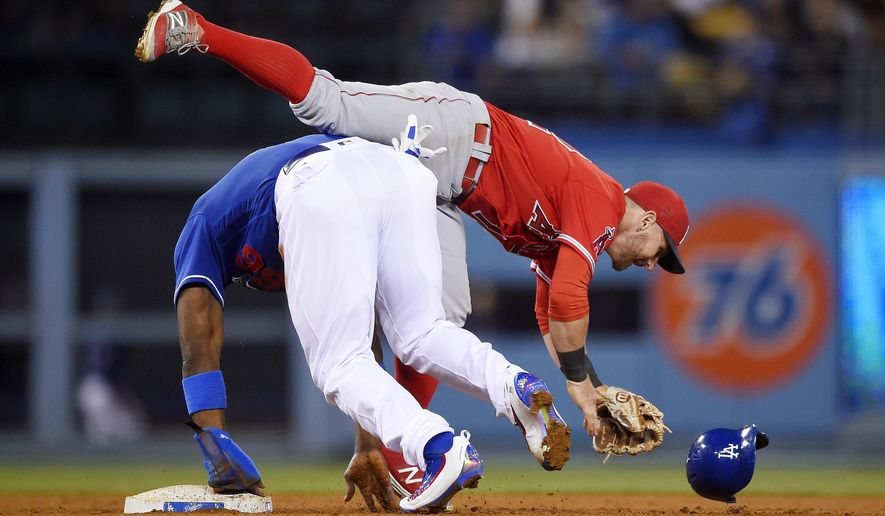 Los Angeles Angels second baseman Johnny Giavotella, top, is upended by Los Angeles Dodgers' Yasiel Puig as Puig steals second and heads to third on a throwing error by catcher Carlos Perez during the fifth inning of an exhibition baseball game, Thursday, March 31, 2016, in Los Angeles. (AP Photo/Mark J. Terrill)