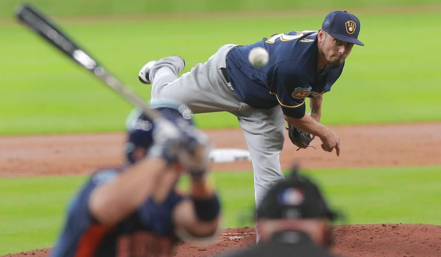 Milwaukee Brewers pitcher Matt Garza delivers a pitch to Houston Astros' Jose Altuve  in the first inning of an exhibition baseball game Friday, April 1, 2016 in Houston.  (AP Photo/Richard Carson)