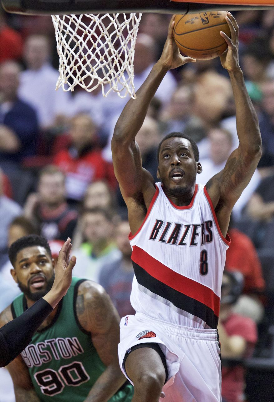 Portland Trail Blazers forward Al-Farouq Aminu, right, dunks in front of Boston Celtics forward Amir Johnson during the second half of an NBA basketball game in Portland, Ore., Thursday, March 31, 2016. (AP Photo/Craig Mitchelldyer)