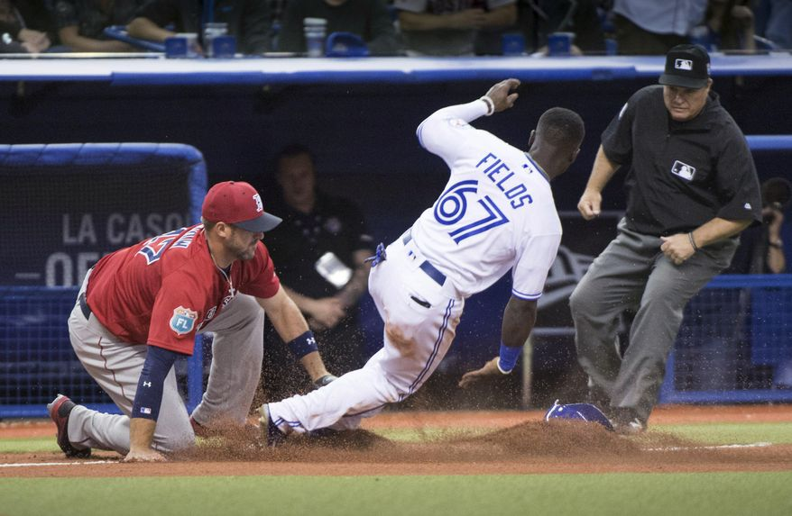 Toronto Blue Jays' Roemon Fields is tagged out while trying to steal third by Boston Red Sox third baseman Travis Shaw as umpire Toby Basner watches during the ninth inning of an exhibition baseball game Friday, April 1, 2016, in Montreal. (Paul Chiasson/The Canadian Press via AP)
