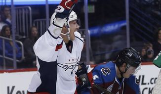 Washington Capitals center Jay Beagle, front, celebrates after scoring a goal past Colorado Avalanche defenseman Chris Bigras in the second period of an NHL hockey game Friday, April 1, 2016, in Denver. (AP Photo/David Zalubowski)