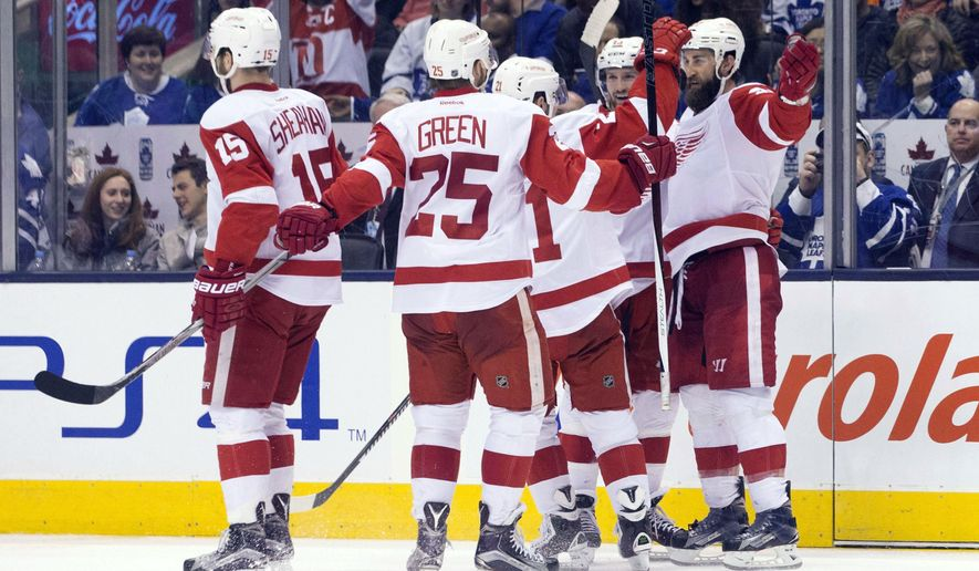 Detroit Red Wings' Kyle Quincey, right, celebrates with teammates after scoring the game winning goal against the Toronto Maple Leafs during third period NHL hockey action in Toronto on Saturday, April 2, 2016. (Chris Young/The Canadian Press via AP)