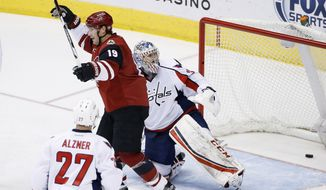 Arizona Coyotes' Shane Doan (19) celebrates his goal against Washington Capitals' Philipp Grubauer, right, of Germany, as Capitals' Karl Alzner (27) watches during the third period of an NHL hockey game Saturday, April 2, 2016, in Glendale, Ariz. The Coyotes defeated the Capitals 3-0. (AP Photo/Ross D. Franklin)