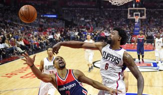 Los Angeles Clippers center DeAndre Jordan, right, blocks the shot of Washington Wizards guard Ramon Sessions during the first half of an NBA basketball game, Sunday, April 3, 2016, in Los Angeles. (AP Photo/Mark J. Terrill)