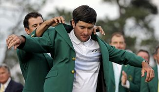 Defending Masters' champion Adam Scott, of Australia, helps Bubba Watson, right, with his green jacket after winning the Masters golf tournament Sunday, April 13, 2014, in Augusta, Ga. (AP Photo/David J. Phillip)