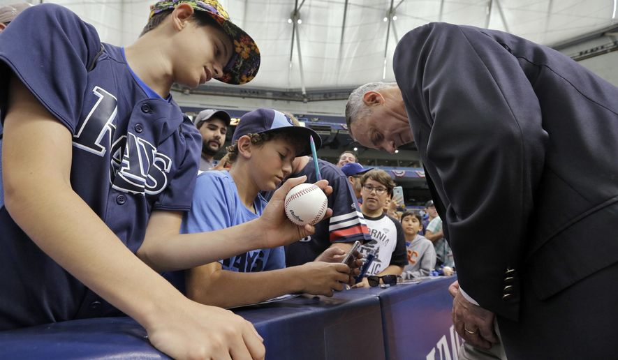 MLB commissioner Rob Manfred, right, gives autographs to fans before a baseball game between the Tampa Bay Rays and the Toronto Blue Jays, Sunday, April 3, 2016, in St. Petersburg, Fla. (AP Photo/Chris O'Meara)
