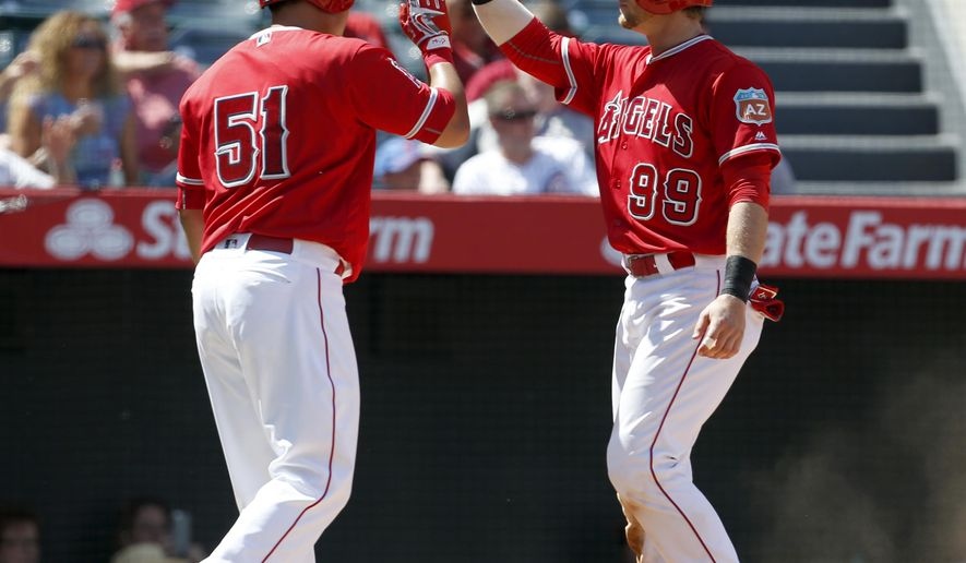 Los Angeles Angels Ji-Man Choi (51) and teammate Taylor Ward celebrate after scoring on a single by David Fletcher in the eighth inning against the Chicago Cubs in an exhibition baseball game in Anaheim, Calif., Sunday, April 3, 2016. (AP Photo/Christine Cotter)