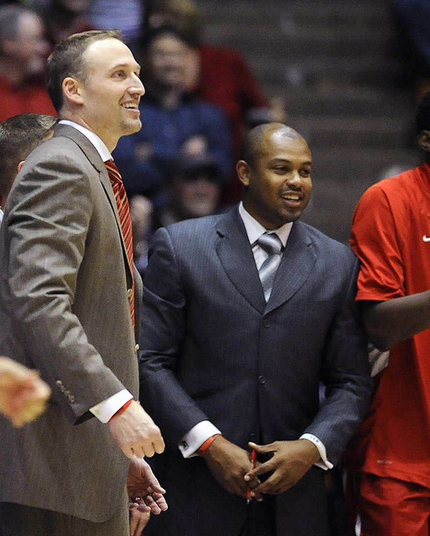FILE - In this Nov. 17, 2013, file photo, Illinois State associate head basketball coach Torrey Ward, right, and head coach Dan Muller smile after a college basketball game in Evanston, Ill. Ward was one of seven people killed in a small plane crash near Bloomington, Ill., one year ago on April 7, 2015, as the plane was returning from the NCAA Final Four tournament. Members of the Illinois State University community continue to grapple with last April's tragedy. (AP Photo/Matt Marton, File)
