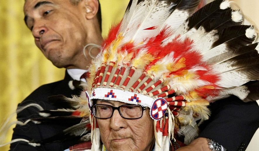 FILE - In this Aug. 12, 2009 file photo, President Barack Obama leans away to avoid the headdress as he presents the 2009 Presidential Medal of Freedom to Joseph Medicine Crow during ceremonies at the White House in Washington. Medicine Crow, the last surviving war chief for Montana's Crow Tribe, died Sunday, April 3, 2016 in a Billings hospice at age 102. Medicine Crow earned the title of war chief and a Bronze Star after stealing enemy horses and other exploits as a U.S. soldier in World War II.(AP Photo/J. Scott Applewhite, File)