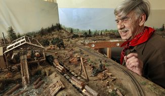 In this photo taken on Wednesday, March 16, 2016, Charles Edwards looks over his model train layout in Alameda, Calif. Edwards, a retired city gardener will be knocking on doors in Alameda to persuade voters to support a citizen initiative to cap rent increases. (AP Photo/Ben Margot)