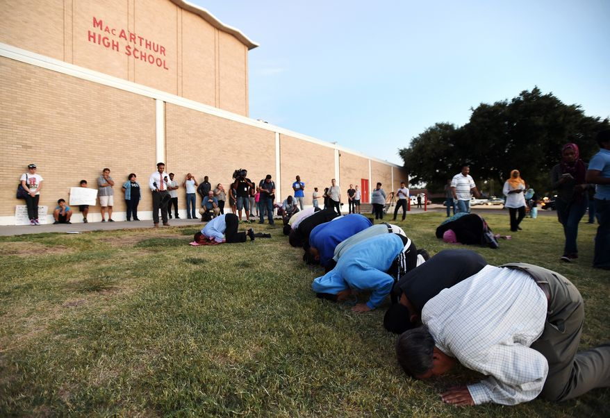 Muslims pray in front of MacArthur High School in Irving, Texas, during a Sept. 17, 2015, prayer vigil in support of Ahmed Mohamed, 14, who was arrested when teachers and police mistook a clock he built for a possible bomb. (Associated Press) **FILE**