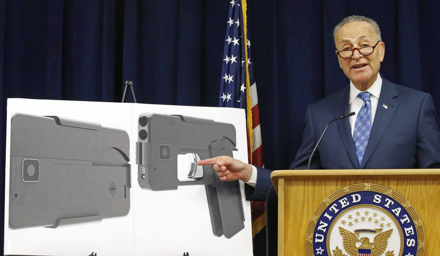Sen Charles Schumer, New York Democrat, points to a photograph of what appears to be a cellphone but is actually a handgun during a news conference in his New York office on April 4, 2016. According to the website of Ideal Conceal, the company that is developing the product, the handgun is a double-barreled .380 caliber gun that can serve as a concealed weapon. (Associated Press)