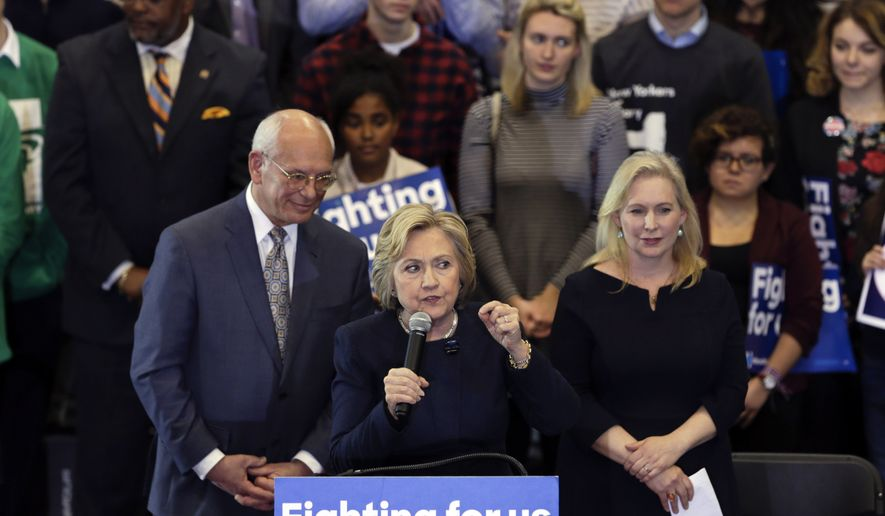 Democratic presidential candidate Hillary Clinton speaks during a rally at Cohoes High School on Monday, April 4, 2016, in Cohoes, N.Y. Rep. Paul Tonko, D-N.Y., left, and Sen. Kirsten Gillibrand, D-N.Y., stand behind Clinton. (AP Photo/Mike Groll)