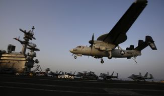 In this Aug. 10, 2014, file photo, an aircraft lands after missions targeting the Islamic State group in Iraq from the deck of the U.S. Navy aircraft carrier USS George H.W. Bush in the Persian Gulf. (AP Photo/Hasan Jamali, File)
