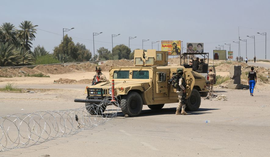 Iraqi army stand guard at the site near of a suicide attack targeting a checkpoint in Baghdad Iraq, Monday, April 4, 2016. A suicide bomber with explosive belt hit a checkpoint on Monday  manned by Iraqi troops in northern Baghdad, killing several people, all of them from security troops. (AP Photo/Karim Kadim)