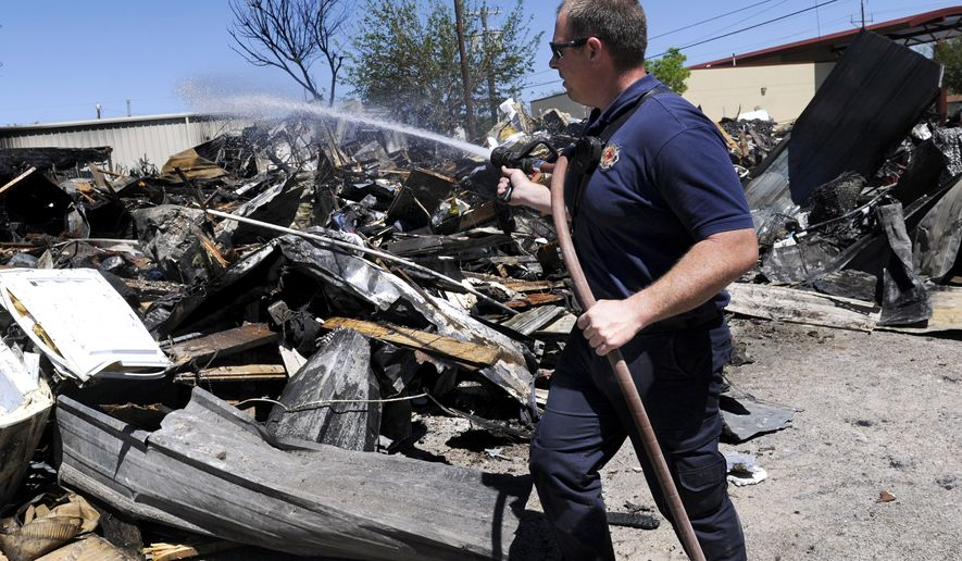 In this Sunday April 3, 2016 photo, Zach Williams of the Abilene Fire Department Station 2 waters down the remains of the Christian Service Center in Abilene, Texas. The facility which supplied clothing, food and household items to those in need, burned to the ground Saturday. (Ronald W. Erdrich/The Abilene Reporter-News via AP) MANDATORY CREDIT