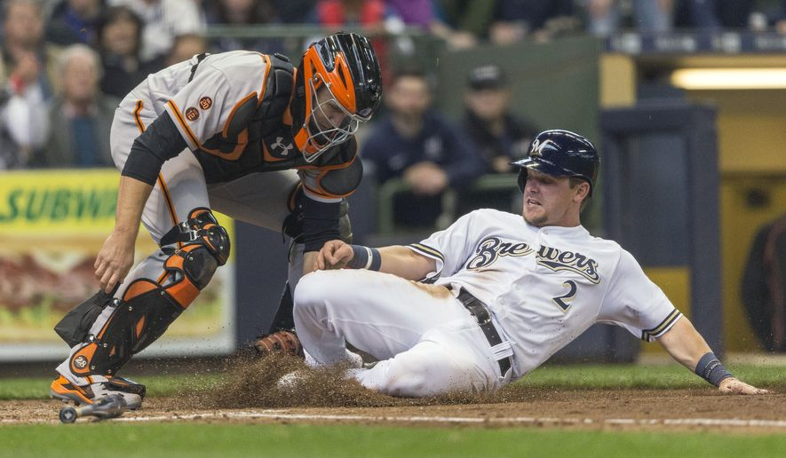 Milwaukee Brewers' Scooter Gennett, right, is tagged out by San Francisco Giants' Buster Posey while trying to score during the fourth inning of a baseball game Monday, April 4, 2016, in Milwaukee. (AP Photo/Tom Lynn)