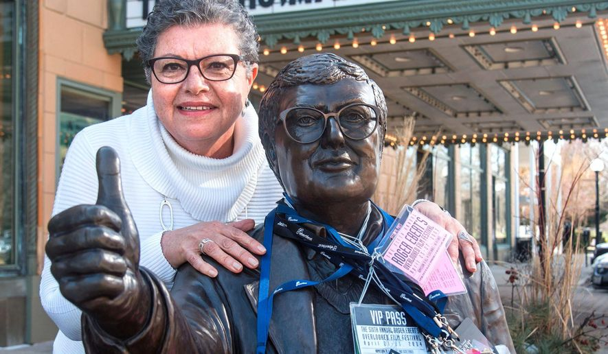 "In this March 15, 2016 photo, Amani Ayad hangs all her Ebertfest passes around a statue of the late film critic outside the Virginia Theatre in Champaign, Ill. Ayad has been a hostess for Roger Ebert's Film Festival guests every year since 2003. She and the more than dozen other hosts pick up their guests and take them back to the airport and to and from their hotel and to festival events. She ferried around a festival guest in 2014 whom she had never heard of before. Two years later Ayad would see the actress, Brie Larson, pick up the Academy Award for best actress for portraying a captive mother in ""Room."" (John Dixon/The News-Gazette via AP ) MANDATORY CREDIT"