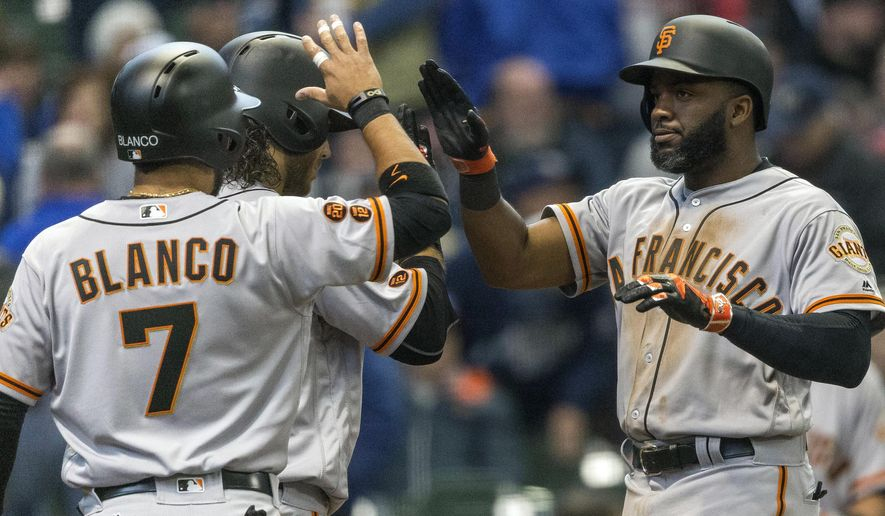 San Francisco Giants' Denard Span, right, is created by teammates Gregor Blanco and Brandon Crawford after hitting a three-run home run off Milwaukee Brewers' Ariel Pena during the eighth inning of a baseball game Monday, April 4, 2016, in Milwaukee. (AP Photo/Tom Lynn)