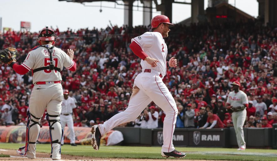 Cincinnati Reds' Zack Cozart (2) scores on a fielding error by Philadelphia Phillies first baseman Ryan Howard (not shown) in the first inning of their opening day baseball game, Monday, April 4, 2016, in Cincinnati. (AP Photo/Gary Landers)