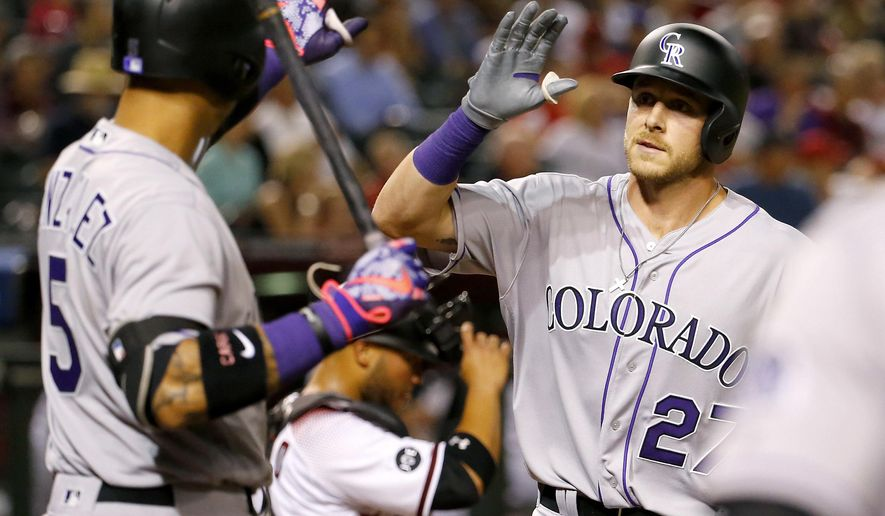 Colorado Rockies shortstop Trevor Story (27) high fives teammate Carlos Gonzalez (5) after hitting his second career home run against the Arizona Diamondbacks during the fourth inning of a baseball game, Monday, April 4, 2016, in Phoenix. (AP Photo/Matt York)
