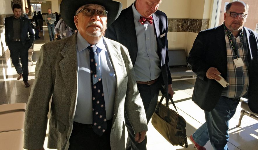 Former New Mexico state Sen. Phil Griego, left, and his attorney Tom Clark, center, walk out of an arraignment in Santa Fe District Court in Santa Fe, N.M., Monday, April 4, 2016. The Democrat from San Jose was released pending trial after pleading not guilty to fraud and bribery charges stemming from his role in the sale of a state-owned building in Santa Fe. (AP Photo/Morgan Lee)