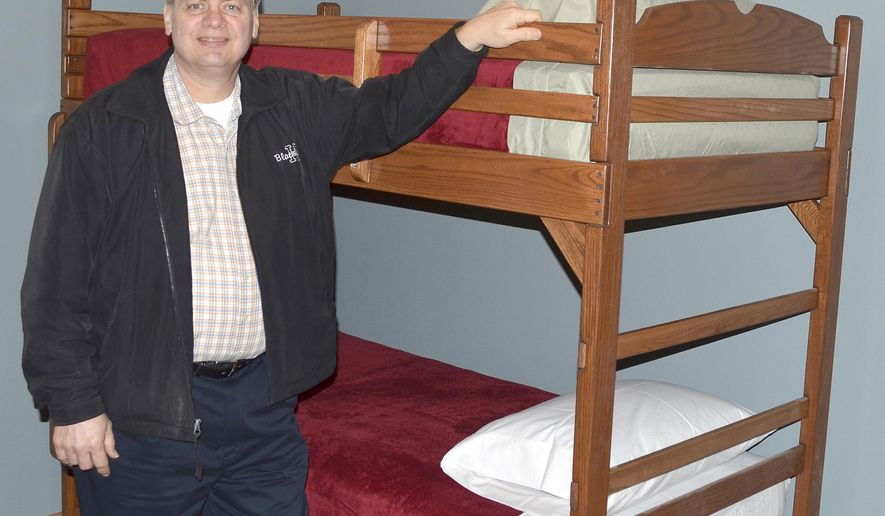 In this April 1, 2016 photo, Harold Youtzy Jr., Sioux City Gospel Mission's executive director and pastor, stands next to one of the bunk beds inside one of the brand-new apartments in the shelter for single men with children in Sioux City, Iowa. The shelter, which will provide single men and their children temporary emergency housing and assistance, will open later this month. (Ian Richardson/Sioux City Journal via AP) MANDATORY CREDIT
