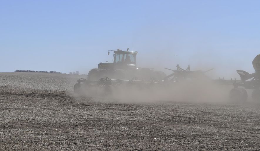 A four-wheel drive tractor pulled a cultivator and a tank of dry fertilizer over a 640-acre field on Monday, March 28, 2016, north of Miller, SD, on Wagner Farms. Owner Gary Wagner said he would plant corn on the field about April 15. Like many South Dakota farmers he's planting less wheat and more corn this year because corn promises better returns in the current market, he said. This year's wheat crop in South Dakota could be the smallest in nearly four decades. (Stephen Lee/Capital Journal via AP)