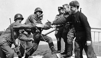 U.S. and Russian troops meet on the wrecked bridge over the Elbe River at Torgau, Germany, on April 26, 1945. The historic rendezvous will be celebrated on its 71st anniversary when the Elbe River Memorial is dedicated. (Associated Press)