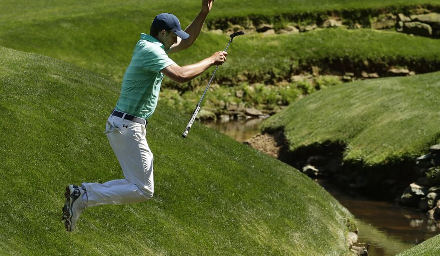 Jordan Spieth jumps over a creek on the 13th fairway during a practice round for the Masters golf tournament, Monday, April 4, 2016, in Augusta, Ga. (AP Photo/Charlie Riedel)