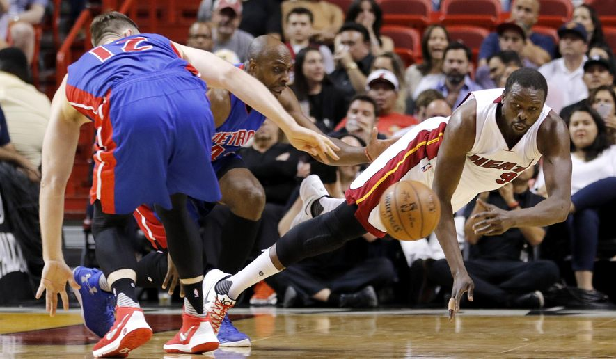 Miami Heat forward Luol Deng (9) passes as he goes to the floor under pressure from Detroit Pistons center Aron Baynes (12) and Detroit Pistons forward Anthony Tolliver, center, in the first quarter of an NBA basketball game, Tuesday, April 5, 2016, in Miami. (AP Photo/Joe Skipper)