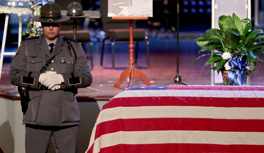 A Georgia state trooper stands watch as an honor guard over the casket of Virginia trooper Chad Dermyer before his funeral Tuesday, April 5, 2016,  at Liberty Baptist Church in Hampton, Va. Authorities say Dermyer was fatally shot by James Brown III at the busy bus terminal, where police were holding a counterterrorism training exercise. (Rob Ostermaier/The Daily Press via AP) MANDATORY CREDIT