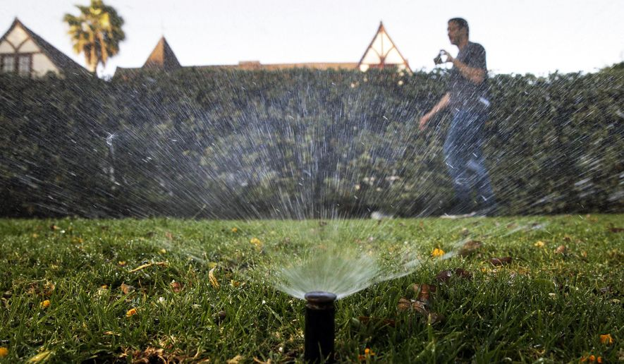 FILE - In this June 5, 2015, file photo, Tony Corcoran records sprinklers watering the lawn in front of a house in Beverly Hills, Calif. In the coming months, state officials will undertake a monumental task of rewriting conservation orders for a fifth year of drought. (AP Photo/Jae C. Hong, File)