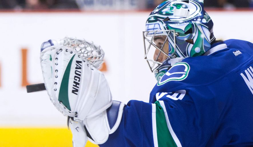 Vancouver Canucks' goalie Ryan Miller makes a glove save against the Los Angeles Kings during the first period of an NHL hockey game in Vancouver, Canada, Monday, April 4, 2016. (Darryl Dyck/The Canadian Press via AP) MANDATORY CREDIT