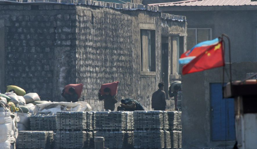 In this Feb. 26, 2016 photo, North Koreans load goods on a dockyard with a Chinese and North Korean national flags in Sinuiju, North Korea, as seen from Dandong in northeastern China's Liaoning province. China on Tuesday, April 5, 2016 imposed restrictions on imports of coal from North Korea and exports of jet fuel to the North in a potentially significant increase in pressure on Pyongyang following U.N. sanctions over its nuclear and missile tests. (Chinatopix via AP) CHINA OUT