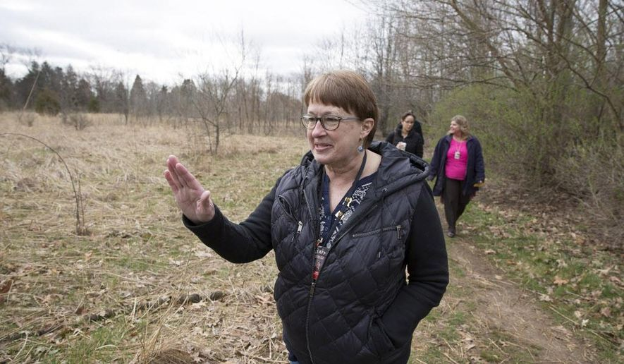 In this photo taken Friday, April 1, 2016, Prairie Vista Elementary School teacher Debbie Baughman walks through the school's prairie and discusses the things she'll teach her third-grade students once it's restored to its original condition in Granger, Ind. (Santiago Flores/South Bend Tribune via AP) MANDATORY CREDIT