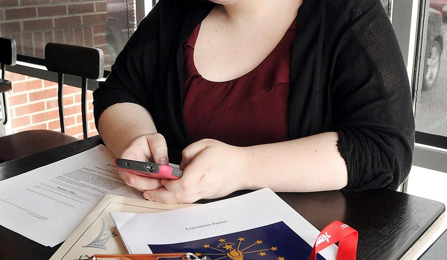 Elwood, Ind. High School senior Megan Stoner is constantly on her phone talking with state legislators hoping to persuade them to vote on a bill she helped author. Shown here March 23, 2016 working from a Anderson, Ind. coffee shop, Stoner hopes the bill, which would reduce Indiana's minimum age to become a state representative or state senator, will pass in the next legislative session. (John P. Cleary/The Herald Bulletin via AP)