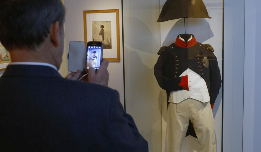 "A visitor takes pictures of Napoleon's clothes presentation during a press visit of the exhibition ""Napoleon in St Helena"" in Paris, France, Tuesday, April 5, 2016. France's national army museum ""Les Invalides"" has recreated the home where Napoleon lived his final years, bringing furniture and belongings from the remote Atlantic Island of St. Helena to central Paris for the first time since he was exiled there 200 years ago. (AP Photo/Francois Mori)"