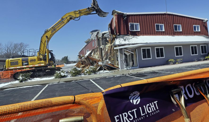 An excavator demolishes a building during an official groundbreaking, Tuesday, April 5, 2016, in Taunton, Mass., where the Mashpee Wampanoag tribe will build a resort casino that it hopes will become Massachusetts' first Las Vegas-style resort. The First Light casino, hotel and entertainment complex will be built on an industrial park that's part of the Cape Cod-based tribe's recently designated federal reservation. (AP Photo/Elise Amendola)
